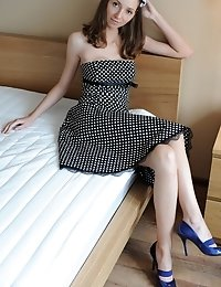 Lovely Chicklette In Black Dress In White Dots Poses On The Bed And Shows Tits And Pussy.